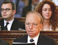 l-r: Coulson, Murdoch, Brooks, shown in a church service in 2005. Photo by Graeme Robertson/Getty