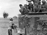A Vietnamese farmer holds the body of his dead child while a group of South Vietnamese soldiers looks on.  Photo: Horst Faas.