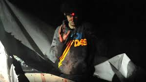 Dhokhar Tsarnaev surrendering, with his forehead marked by a sniper's infrared.